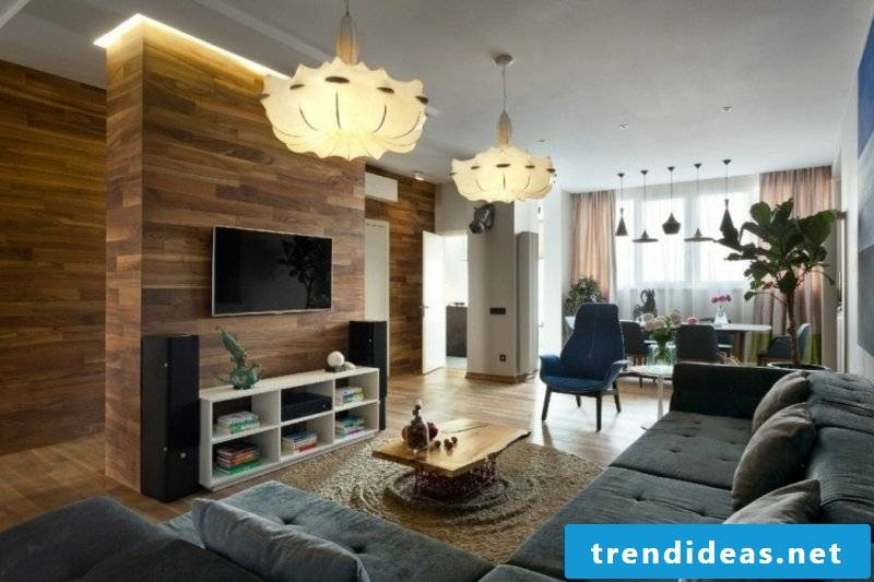 Living room with wooden wall paneling and gray corner sofa