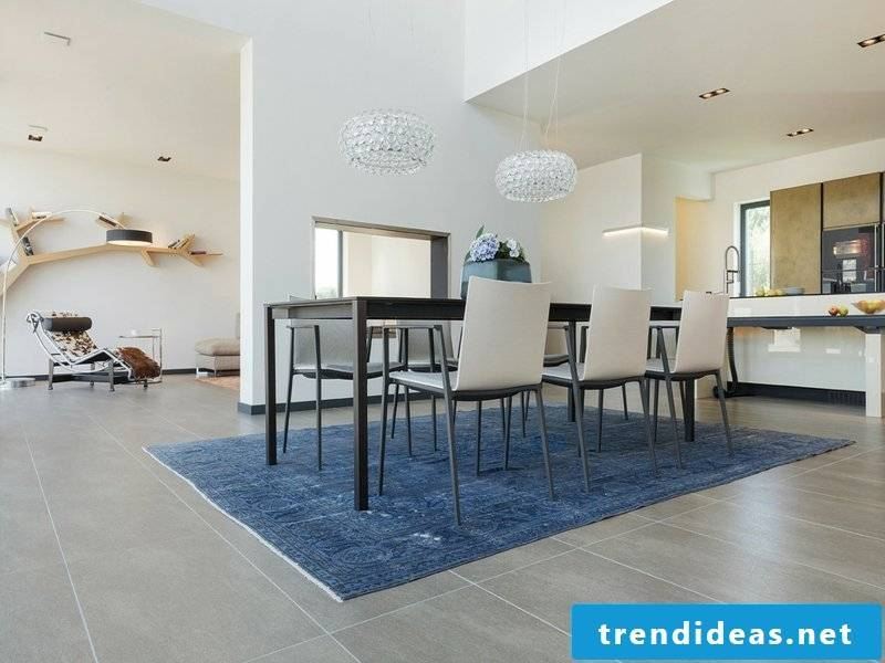 Rough white dining room lamps over blue carpet