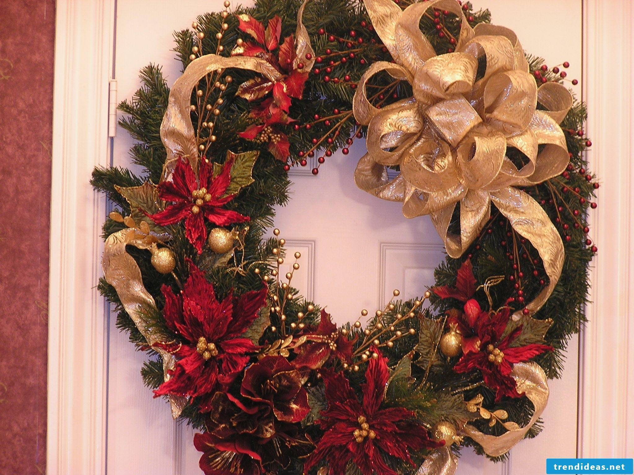 pretty door wreath Christmas with poinsettias and golden bows