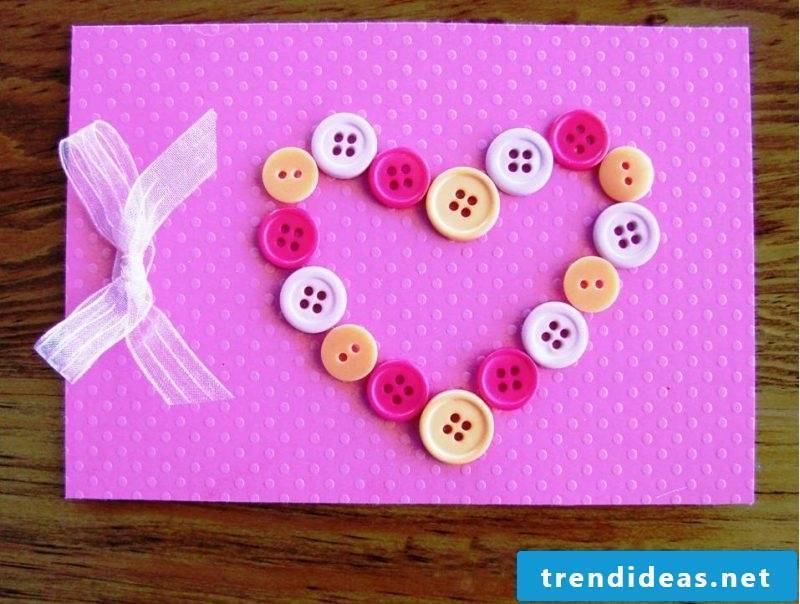 birthday cards design on pink paper with a creative heart out of knots