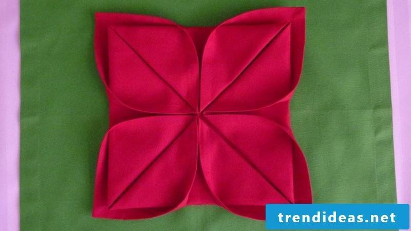 Folding a flower from the napkins.