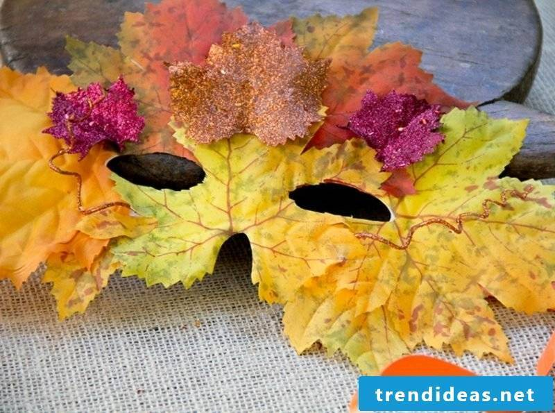 Autumn decoration made with the children mask from autumn leaves