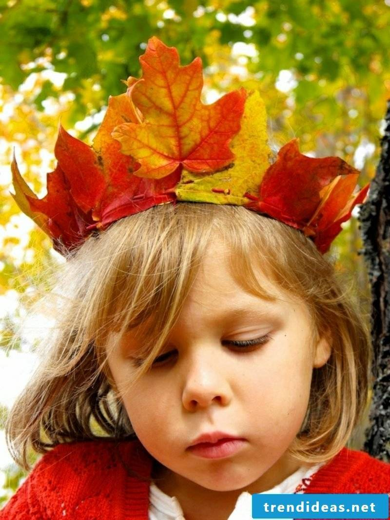 Autumn decoration made with the children crown of colorful leaves