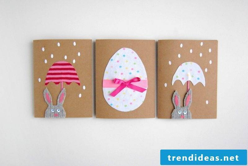 Easter cards on hard paper with eggs and bunnies with umbrella and pink ribbon