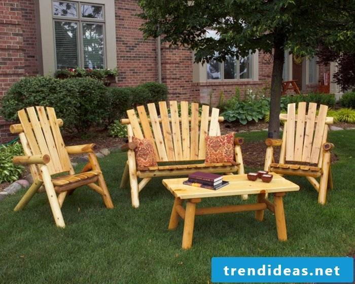 massive-garden furniture-three-chair-set-table-wood-cushion-pattern reference-books-candles-vorgarten