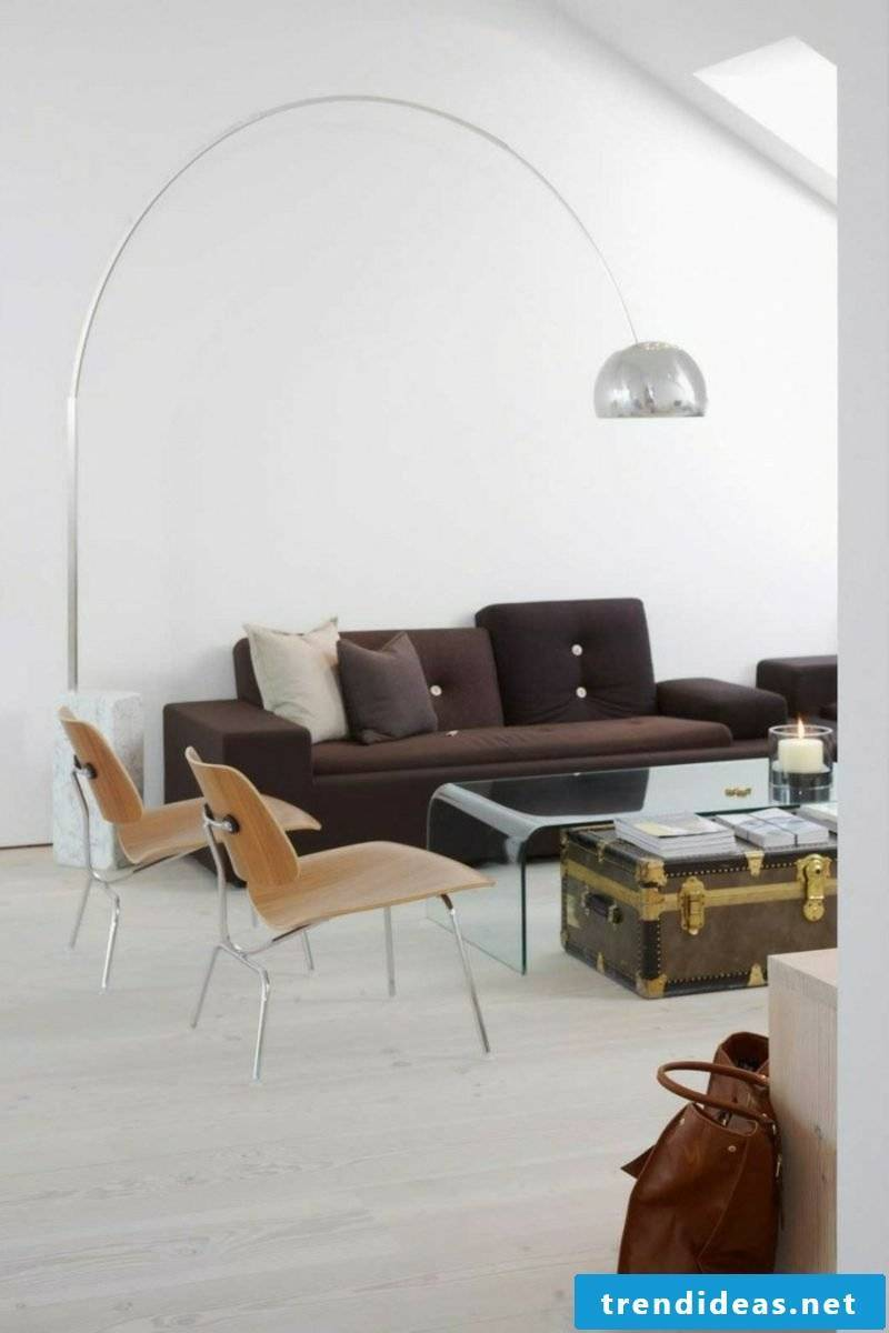 Scandinavian furniture Soft upholstered sofa in chocolate brown Original lamp made of precious steel Coffee table made of old suitcase