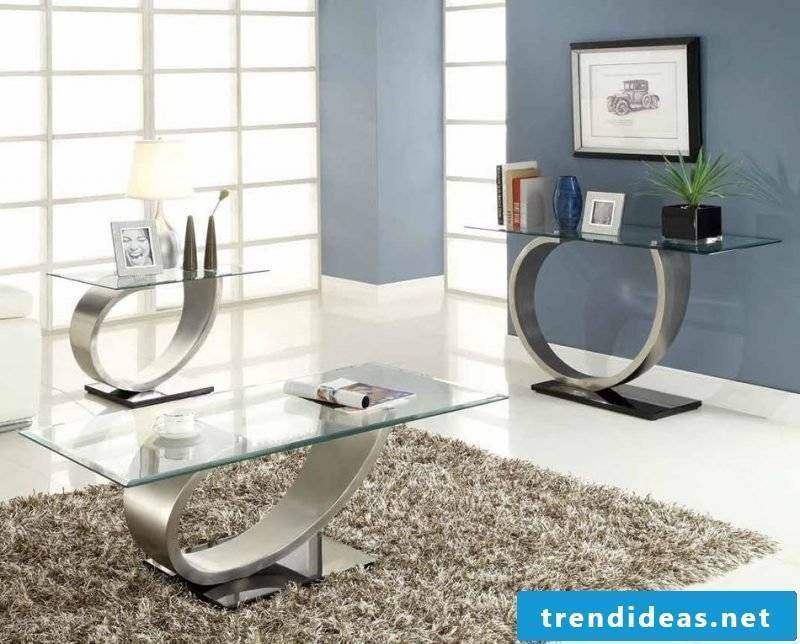 Modern silver tables with glass top.
