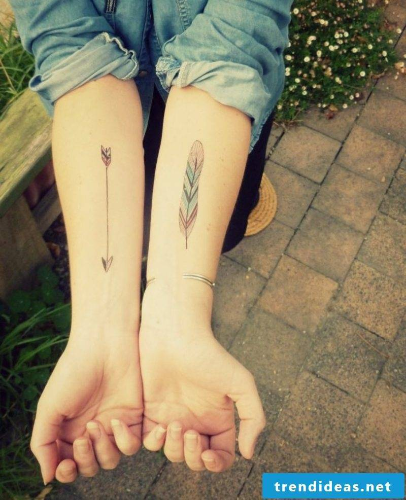 small tattoo motifs feather and arrow forearm