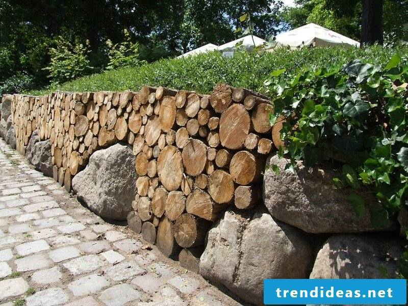 interesting garden wall made of wood and massive stones