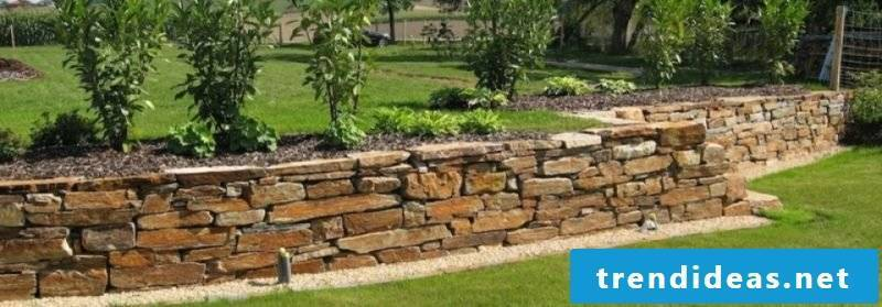 Stone wall in the garden bed border