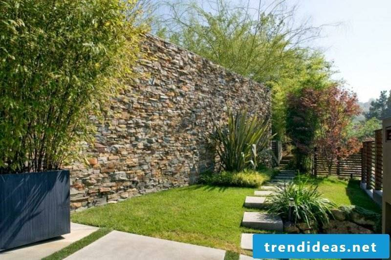 high stone wall as a blind in the garden