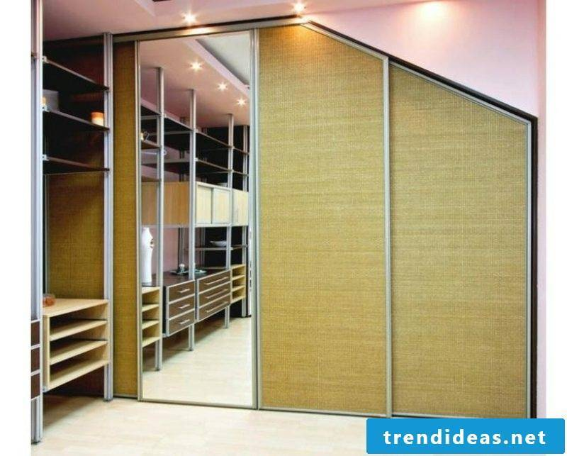 walk-in closet under sloping roof with mirror