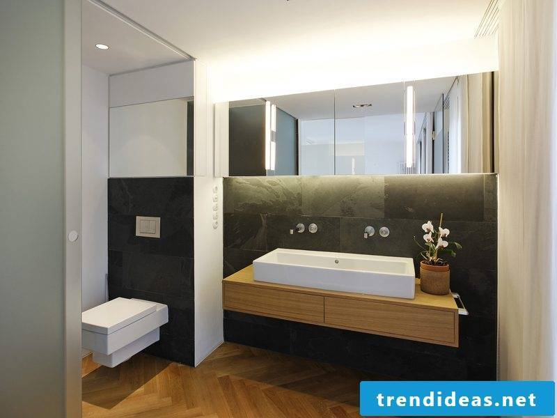 wooden vanity top in modern bathroom with black tiles and soft lighting