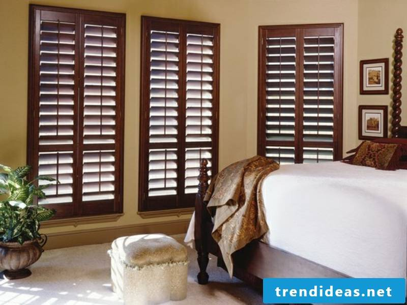 Bedroom with wooden blinds in a dark color